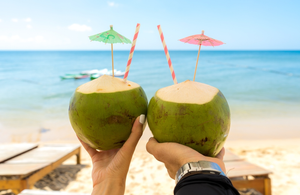 bride and groom holding coconut