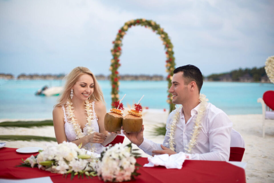bride and groom sharing coconuts